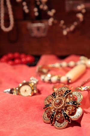 Beautiful golden brooch on red surface and more jewelry in the background photo