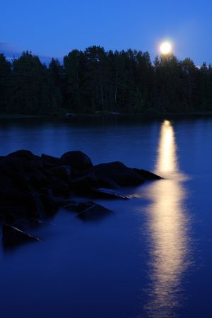 Moon rising and reflecting in the still water of a lake