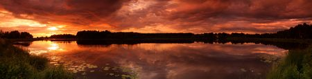 Panorama of lake at sunset with reflection in Finland