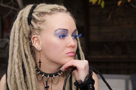 Young woman wearing punk clothing and makeup in deserted location photo