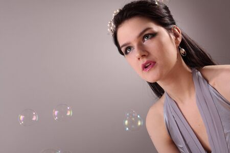 Beautiful fashion model in studio and soap bubbles photo