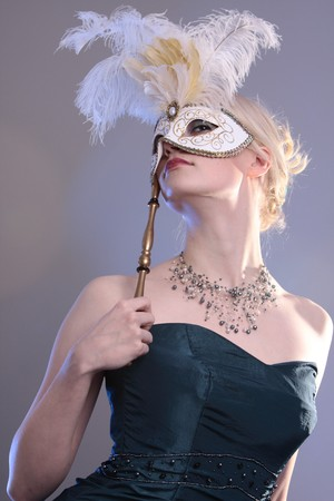 Beautiful young woman with Venetian mask, studio photo