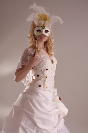Beautiful model wearing a wedding dress and Venetian mask, studio Stock Photo - 4257400