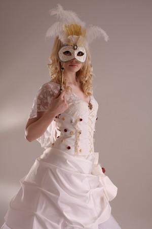 Beautiful model wearing a wedding dress and Venetian mask, studio Stock Photo - 4257400