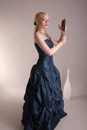 Beautiful young woman wearing a blue prom dress and silver mirror photo