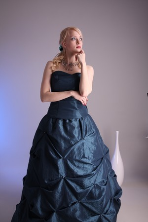 Beautiful young woman wearing a blue prom dress Stock Photo
