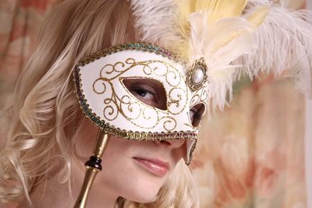 Beautiful model wearing a wedding dress and Venetian mask, studio Stock Photo