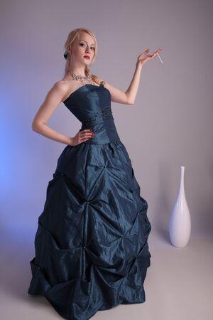 Beautiful young woman wearing a blue prom dress photo