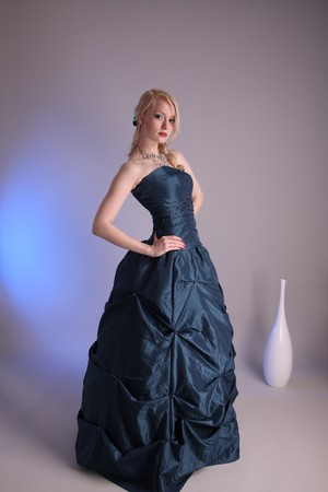 Beautiful young woman wearing a blue prom dress photo