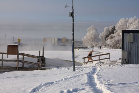 Very cold day, view over a river in Finland and woman coming out of the water Stock Photo - 5084941