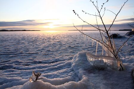Sunset over frozen lake in winter, Finland photo