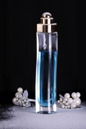 parfum: Tall perfume bottle with blue liquid in studio lighting Stock Photo