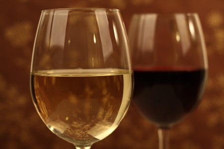 Wine glasses against a brown background with flower pattern Stock Photo