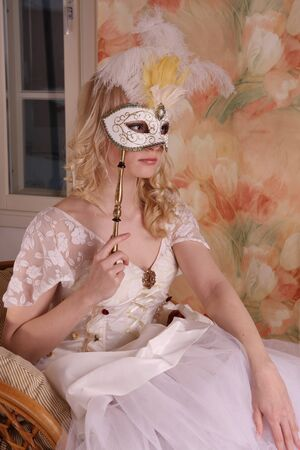 Beautiful model wearing a wedding dress and Venetian mask, studio photo