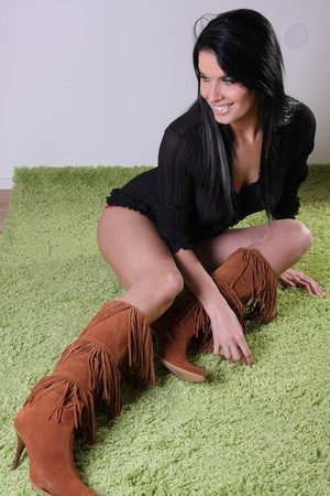 suede: Beautiful woman wearing a black shirt,brown leather boots on a green carpet