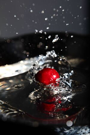 Shiny water splash with cherry falling in the water photo
