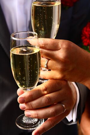 wedding ring hands: Bride and groom holding champagne glasses and toasting Stock Photo