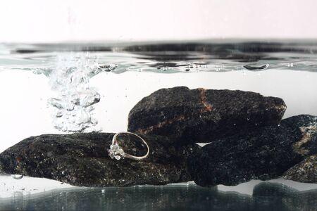 brilliant   undersea: white gold ring underwater on black stones Stock Photo