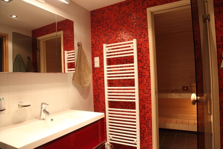 Modern Finnish bathroom with sauna, red tiles and heater photo