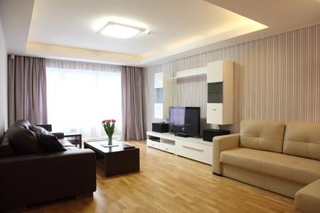 A modern livingroom inside a new flat with modern lighting