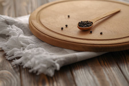 Allspice black pepper in wooden spoon on a cutting board. Kitchen towel and rustic wooden table