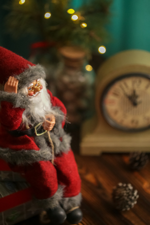 Toy Santa Claus sitting with gifts and Christmas decorations. Happy New Year coming