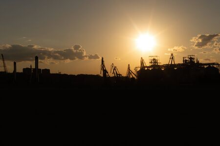Silhouette of a cargo port at sunset on the Black Sea coast, Odessa, Ukraine. View from afar on loading cranes and containers Фото со стока