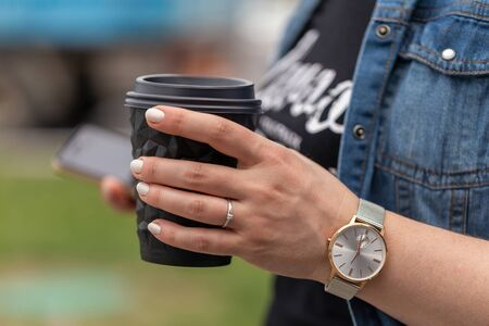 Close up of womens hands holding smartphone and a cup of coffee. A woman is dressed in a blue denim jacket, a black T-shirt and a watch on her arm