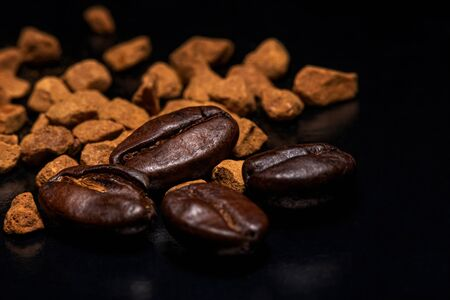 Coffee beans and instant coffee granules on a dark background, macro, close-up