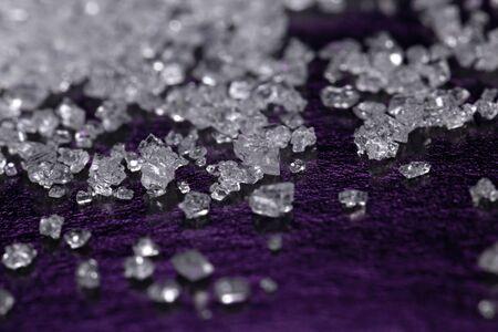 White sugar crystals on a dark violet background, macro, close-up Фото со стока