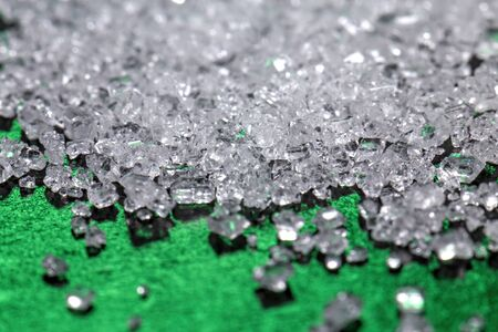 White sugar crystals on a dark green background, macro, close-up