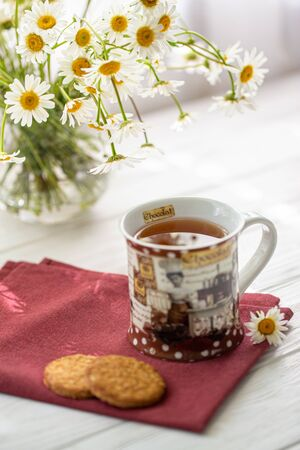 Still life with a cup of tea, cookies and daisies on a wooden background in morning sunlight