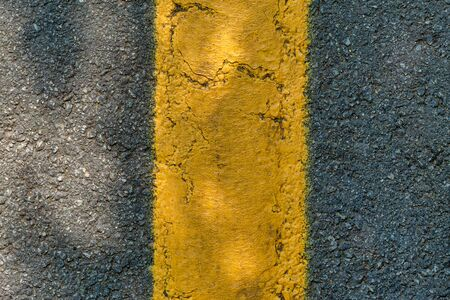 Asphalt texture with a yellow dividing strip and a shadow from foliage on a sunny day. Top view