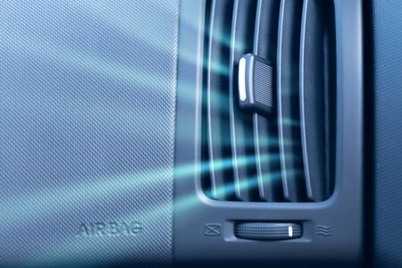 Car air conditioner with passenger airbag and illustration of cold air flow from it. Front view close up