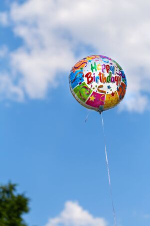 Colorful happy birthday balloon on a blue sky background in summertime Imagens
