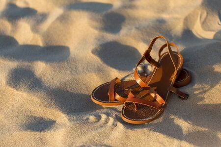 Elegant brown womens leather sandals on the sand of sea beach at early morning sunrise