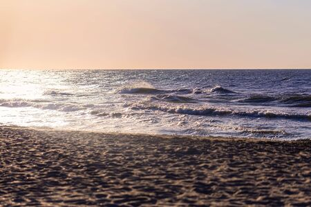 Sea horizont and sand beach at early morning sunrise. Small waves in sunlight