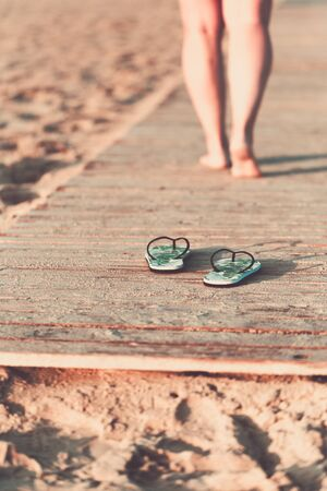 Bare feet of a girl walking on a wooden floor on the seashore at sunny summer morning. Green flip flops in the foreground. Фото со стока