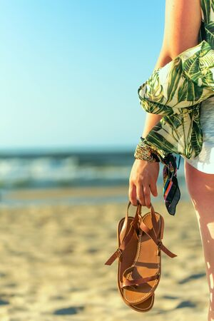 Woman holds brown leather sandals in her hand and looks at the sea. Early morning at the seashore Фото со стока