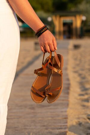 Woman holds brown leather sandals in her hand and looks at the beach hotel. Early morning at the seashore