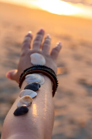 Woman holds seashells on her hand and points towards the sea. Sunrise on the beach in the early morning