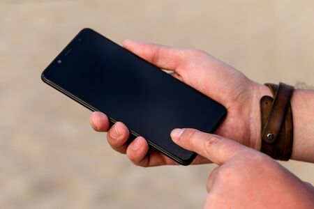 A man touching smartphone screen with his index finger on a beach sand background