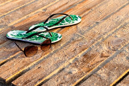 Green flip flops and sunglasses on the wooden boards covered with the beach sand. Close-up, early morning golden sunrise
