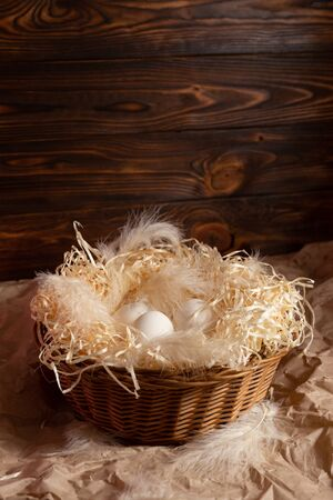 Chicken eggs lie on a wicked paper straw in a wicker basket on a dark wooden background in the morning sun