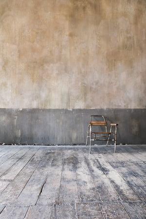 wooden chair in grungy interior. Loneliness, estrangement, alienation concept.