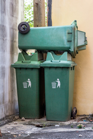Large green wheelie bin stacked not in use.