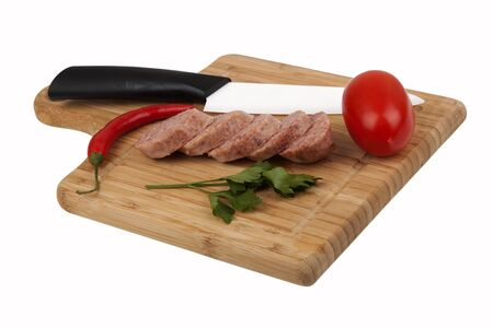 Sausage, pepper, tomato and  knife on kitchen board isolated on white background photo