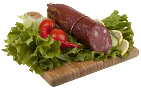 Sausage with vegetables on  kitchen board isolated on white background photo