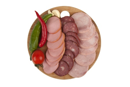 slices of ham and sausage with vegetables on  kitchen board isolated on white background photo