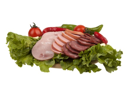 slices of ham and sausage with vegetables on  kitchen board isolated on white background Stock Photo - 17901356